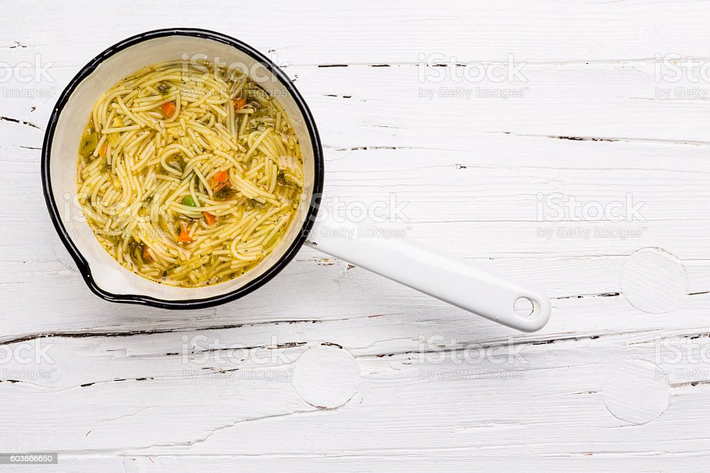 Instant soup in saucepan on wooden background. stock photo