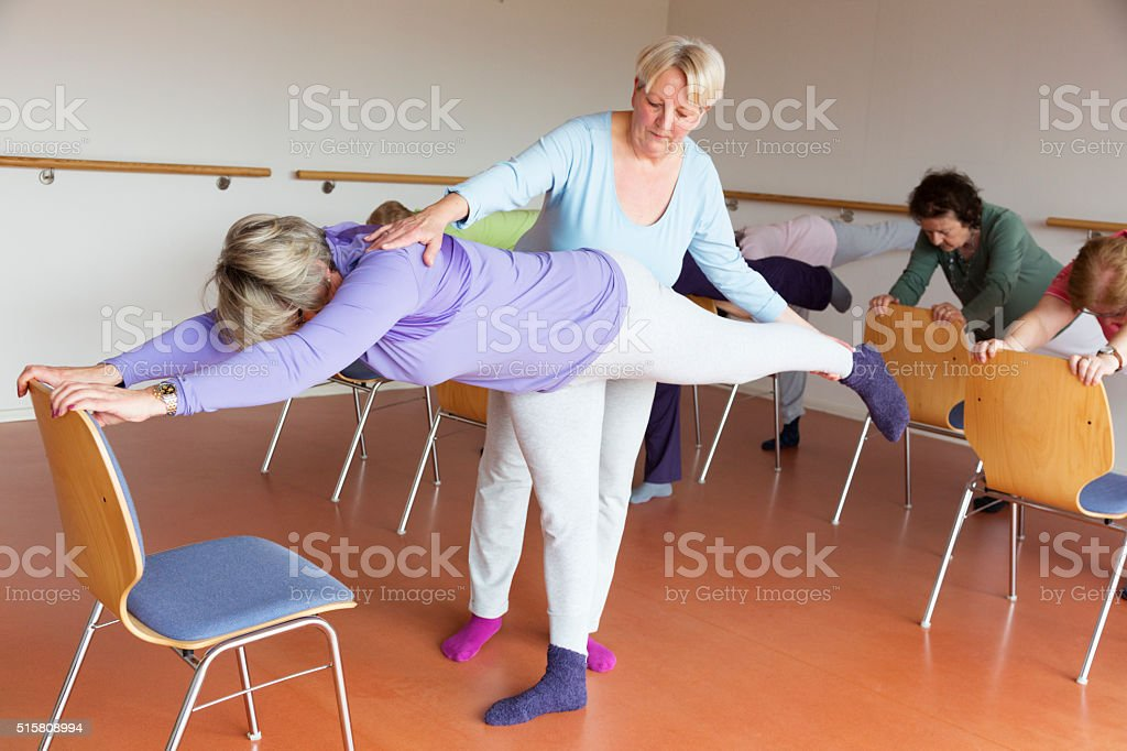 instructor and active senior women in yoga class with chairs stock photo