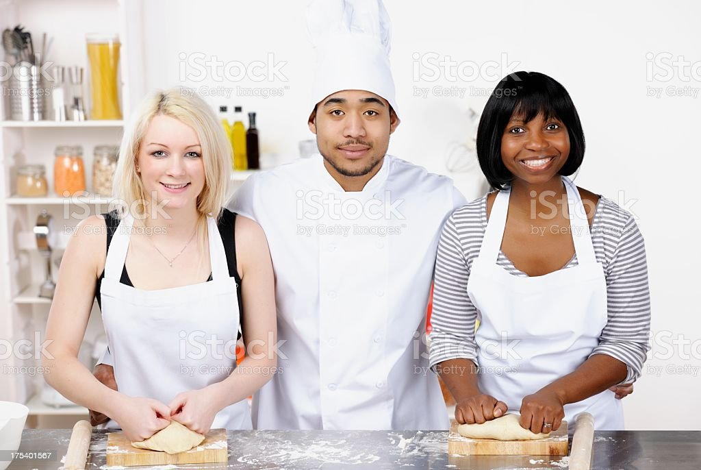 Instructor And Appentices/ Students Enjoying Progress In A Commercial Kitchen royalty-free stock photo