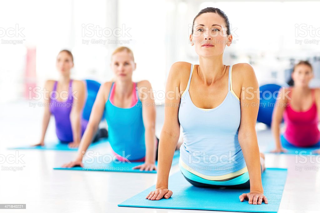 Instructor And Customers Practicing Yoga Exercise In Gym stock photo