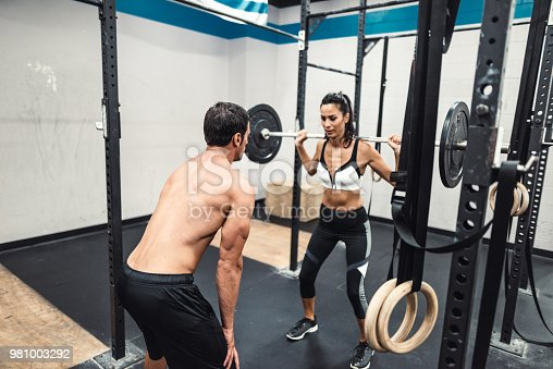 610237160 istock photo instructor and fitness woman doing squats 981003292