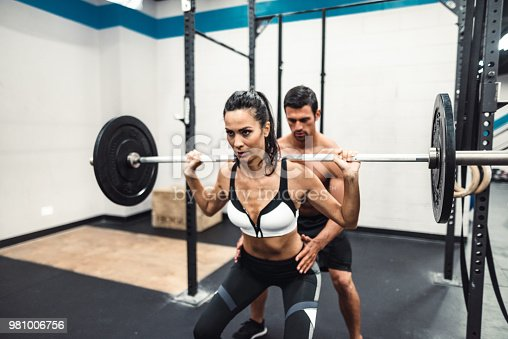 610237160 istock photo instructor and fitness woman doing squats 981006756