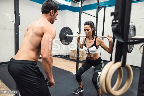 610237160 istock photo instructor and fitness woman doing squats 981007086
