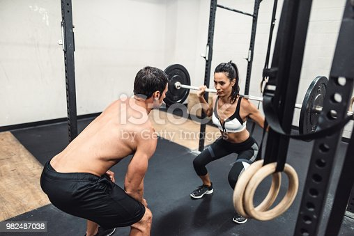 610237160 istock photo instructor and fitness woman doing squats 982487038