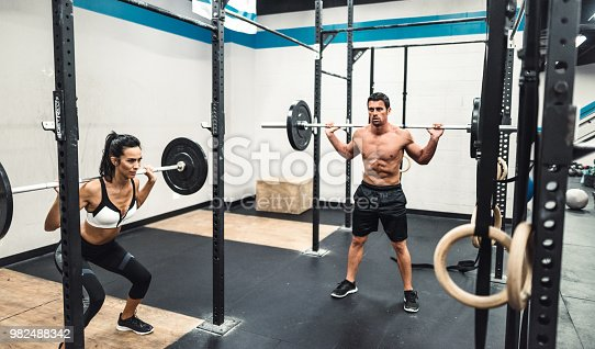 610237160 istock photo instructor and fitness woman doing squats 982488342
