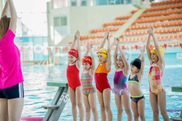 Instructor and group of children doing exercises near a swimming pool stock photo