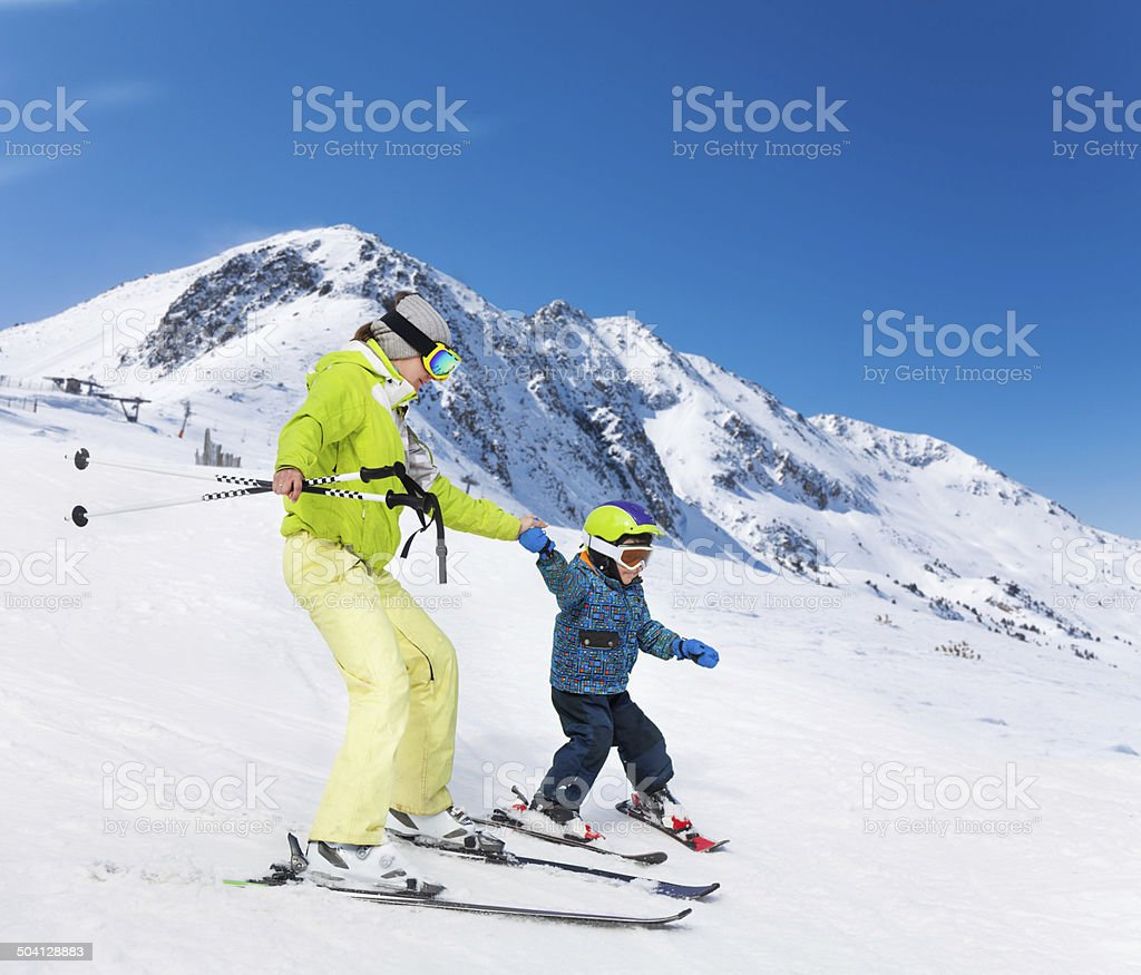 Instructor and kid skiing down the mountain stock photo