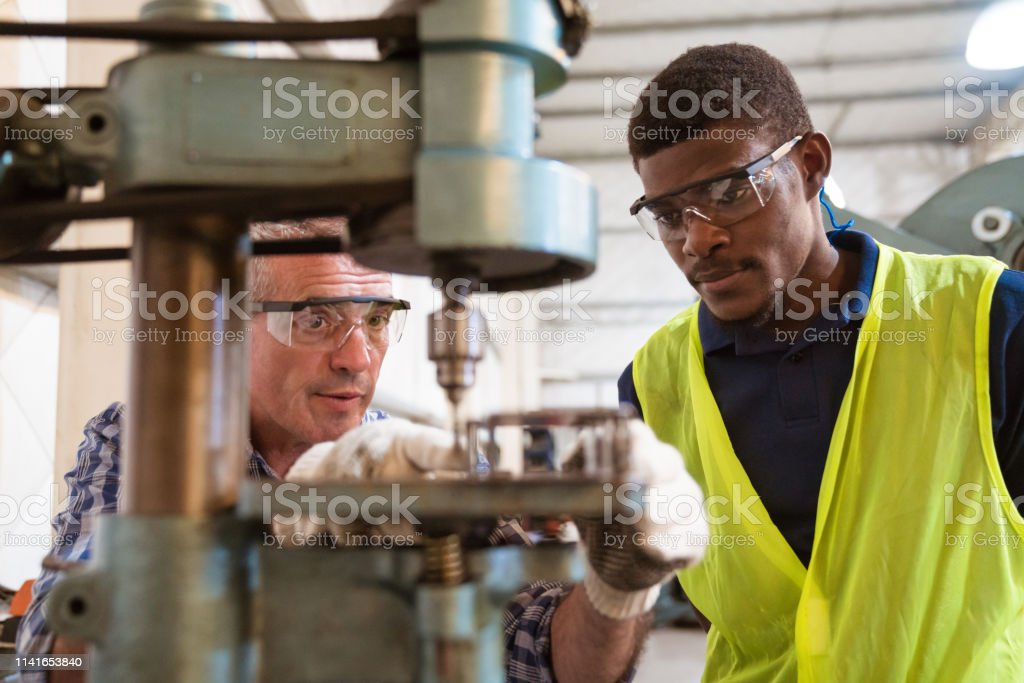 Instructor and trainee discussing over machinery Engineer guiding apprentice in using yoke machine. Instructor is teaching male apprentice in factory. They are working in industry. 25-29 Years Stock Photo