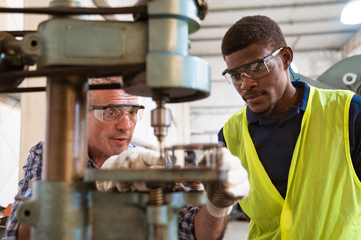 Instructor And Trainee Discussing Over Machinery Stock Photo - Download Image Now