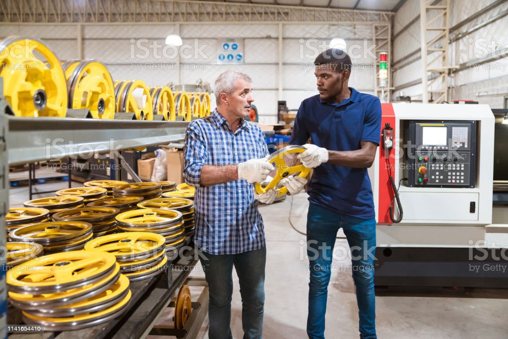 Instructor and trainee holding wheel in factory Male instructor and trainee holding yellow wheel. Engineer is with apprentice in industry. They are standing in factory. 25-29 Years Stock Photo