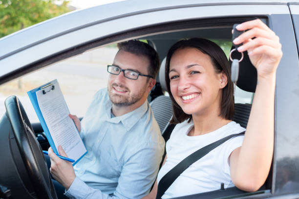 Instructor and young female student, driving lesson Instructor of driving school giving exam while sitting in car driving instructor stock pictures, royalty-free photos & images