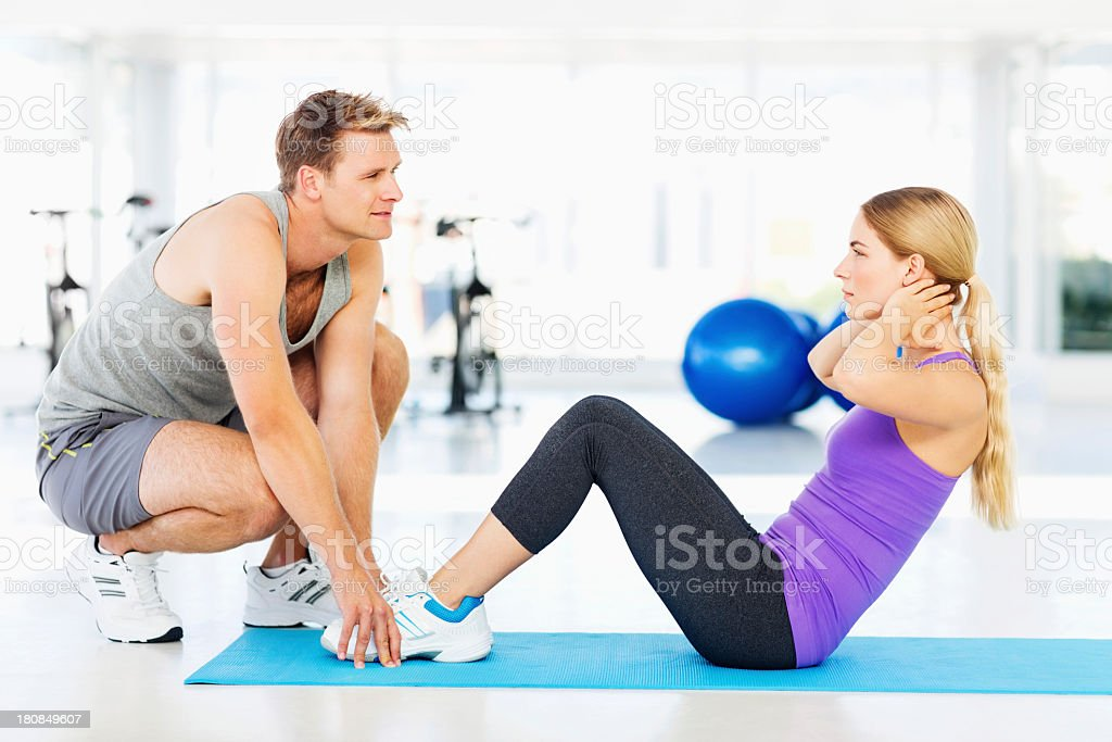 Instructor Assisting Woman Doing Sit-Ups In Health Club royalty-free stock photo