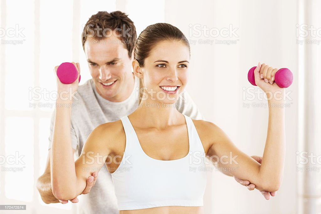 Instructor Assisting Woman In Picking Up Dumbbells royalty-free stock photo