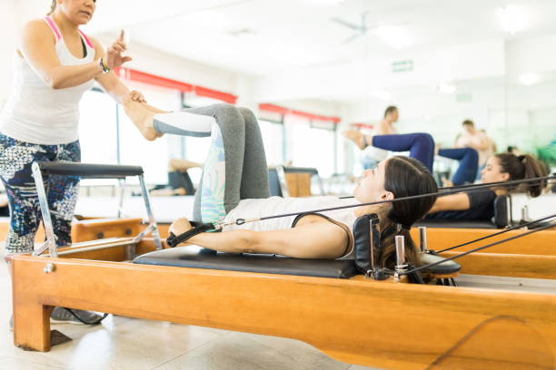 instructor assisting woman on reformer machine in gym - metodo pilates foto e immagini stock