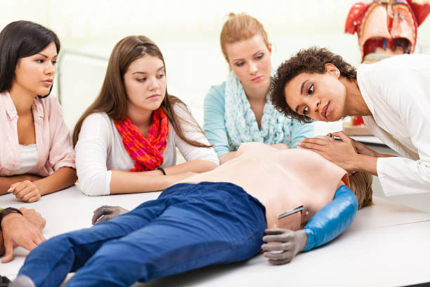 Instructor demonstrates CPR to medical students Female instructor demonstrating chest compressions on a CPR dummy. ventriloquist's dummy stock pictures, royalty-free photos & images