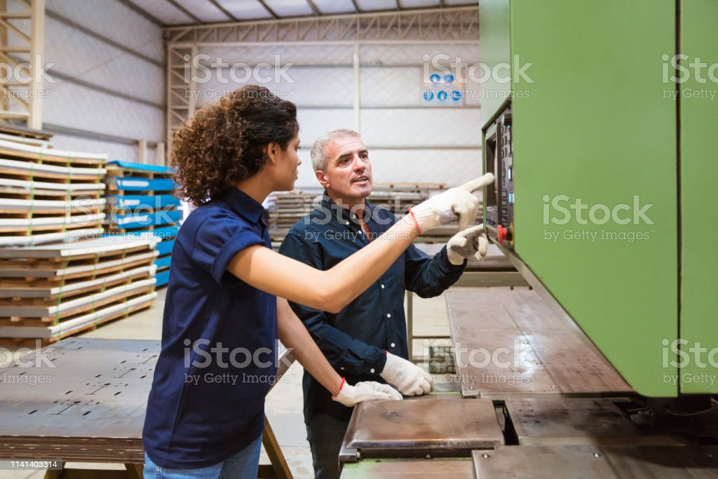 Instructor discussing with trainee in factory Mature engineer and female trainee discussing over puller machine. Instructor is teaching apprentice in factory. They are in industry. 30-34 Years Stock Photo