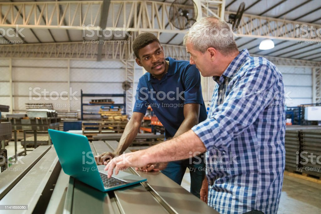 Instructor discussing with trainee over laptop Mature instructor discussing with male apprentice over laptop. Apprentice is listening to engineer at factory. They are working in industry. 25-29 Years Stock Photo