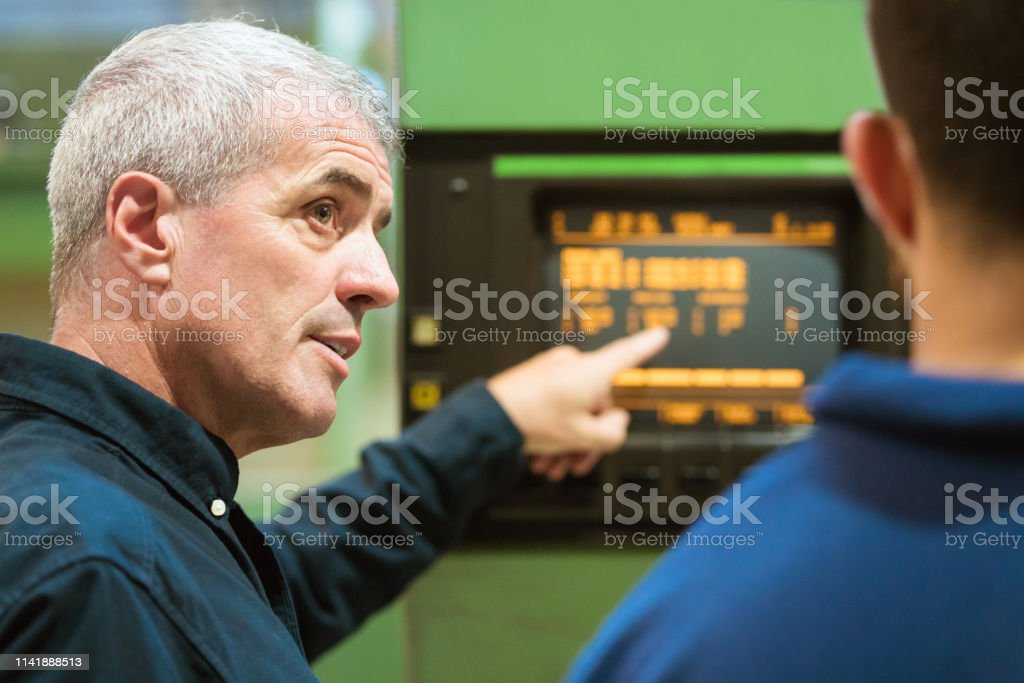 Instructor explaining apprentice in factory Male instructor explaining puller machine to apprentice in industry. Mature man is with young trainee in factory. He is pointing at machinery. 20-24 Years Stock Photo