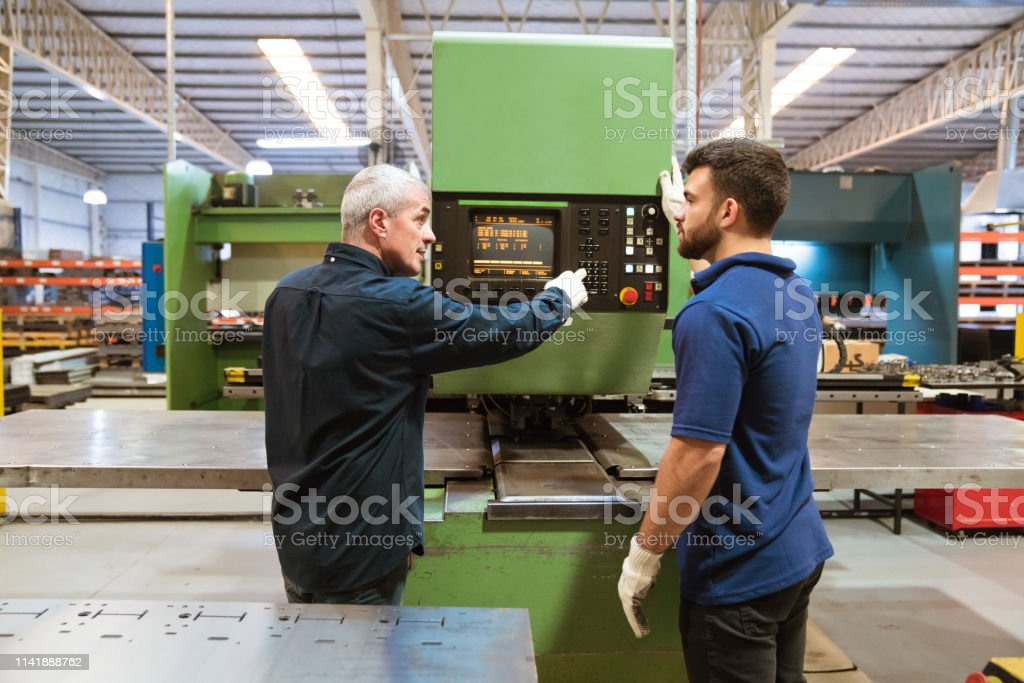 Instructor explaining apprentice in factory Male instructor explaining puller machine to trainee. Mature man is with apprentice in factory. They are working in industry. 20-24 Years Stock Photo