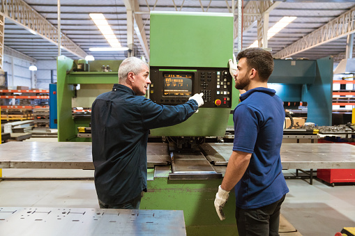 Instructor Explaining Apprentice In Factory Stock Photo - Download Image Now