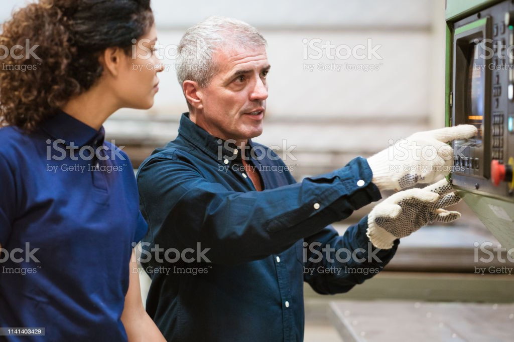 Instructor explaining apprentice in industry Male instructor explaining female apprentice over puller machine in industry. Mature man with trainee in factory. They are looking at machinery. 30-34 Years Stock Photo