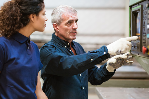 Instructor Explaining Apprentice In Industry Stock Photo - Download Image Now