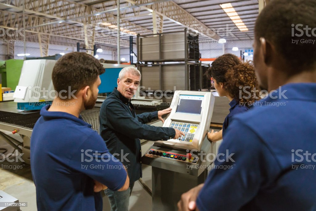 Instructor explaining apprentices in industry Male instructor discussing with trainees over puller machine. Confident engineer is teaching apprentices in industry. They are working in factory. 20-24 Years Stock Photo