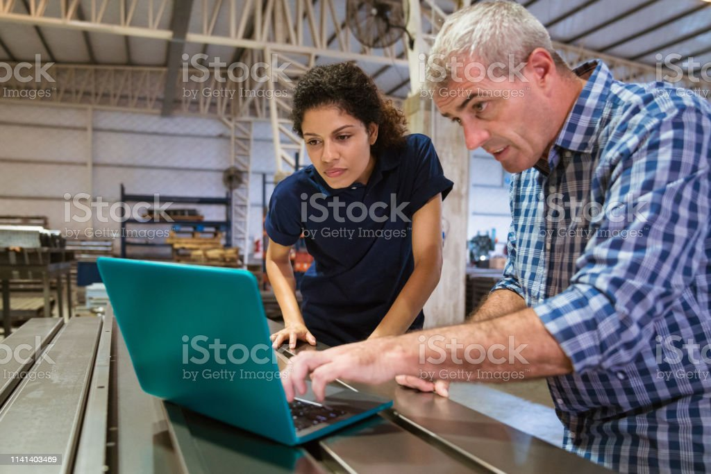 Instructor explaining female trainee over laptop Mature instructor explaining female apprentice over laptop. Trainee is listening to engineer at factory. They are working in industry. 30-34 Years Stock Photo