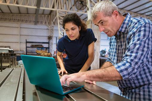 Instructor Explaining Female Trainee Over Laptop Stock Photo - Download Image Now