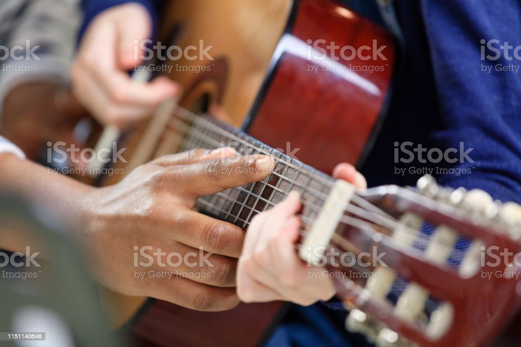 Instructor explaining guitar strings to student Cropped image of music trainer explaining guitar strings to student on fretboard. Pre-adolescent girl is learning musical instrument in class. They are at conservatory. 10-11 Years Stock Photo