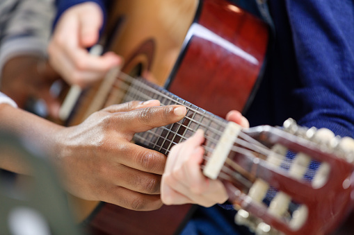 Instructor Explaining Guitar Strings To Student Stock Photo - Download Image Now