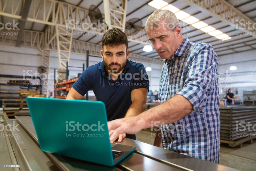 Instructor explaining male trainee over laptop Mature instructor explaining male apprentice over laptop. Trainee is listening to engineer at factory. They are in industry. 20-24 Years Stock Photo