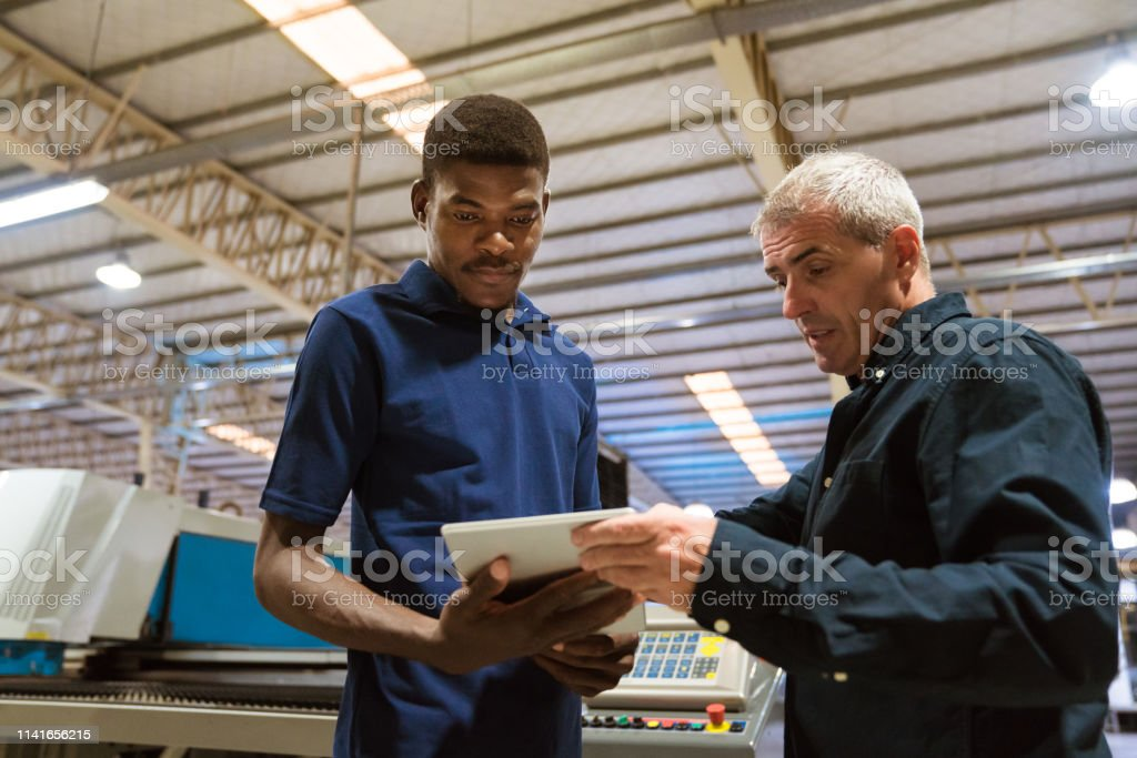 Instructor explaining trainee over digital tablet Male instructor explaining trainee over digital tablet. Engineers are discussing in factory. They are working in industry. 25-29 Years Stock Photo