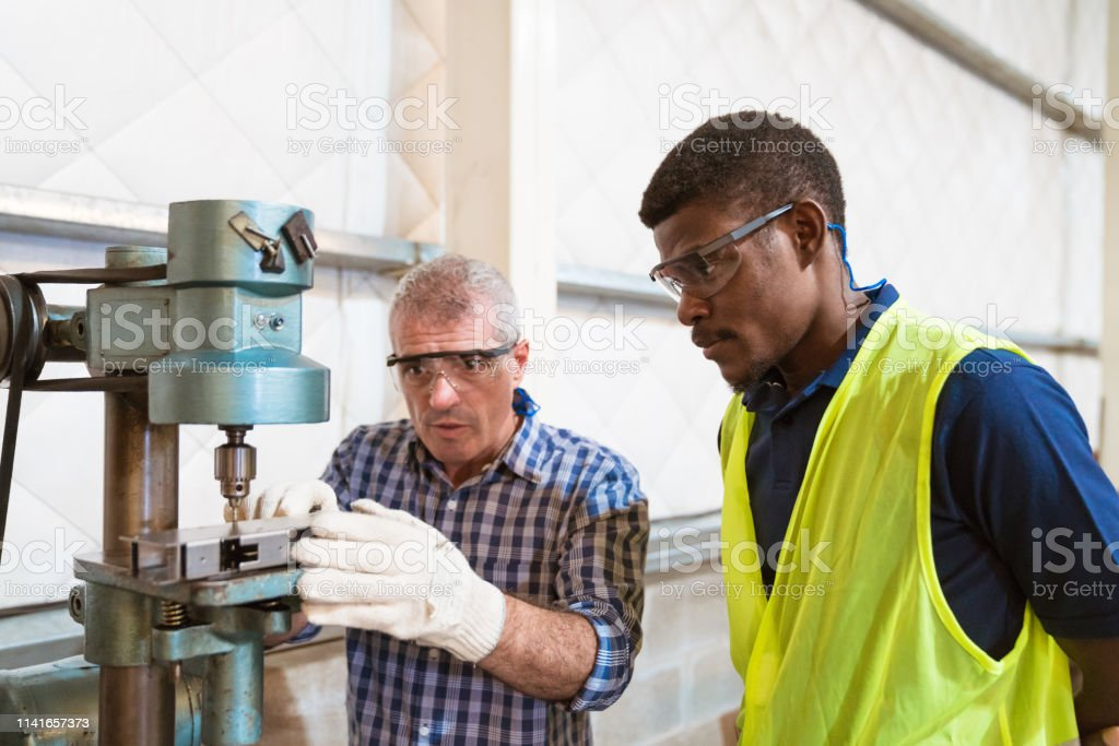 Instructor explaining trainee over yoke machine Mature instructor guiding trainee in using yoke machine. Engineer teaching male apprentice in industry. They are working in factory. 25-29 Years Stock Photo
