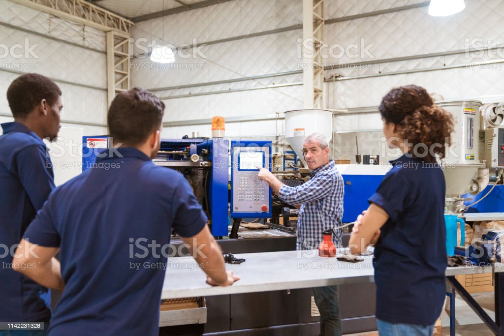 Instructor explaining trainees in factory Instructor explaining apprentices over injector machine. Trainees are listening to engineer in industry. They are standing in factory. 20-24 Years Stock Photo