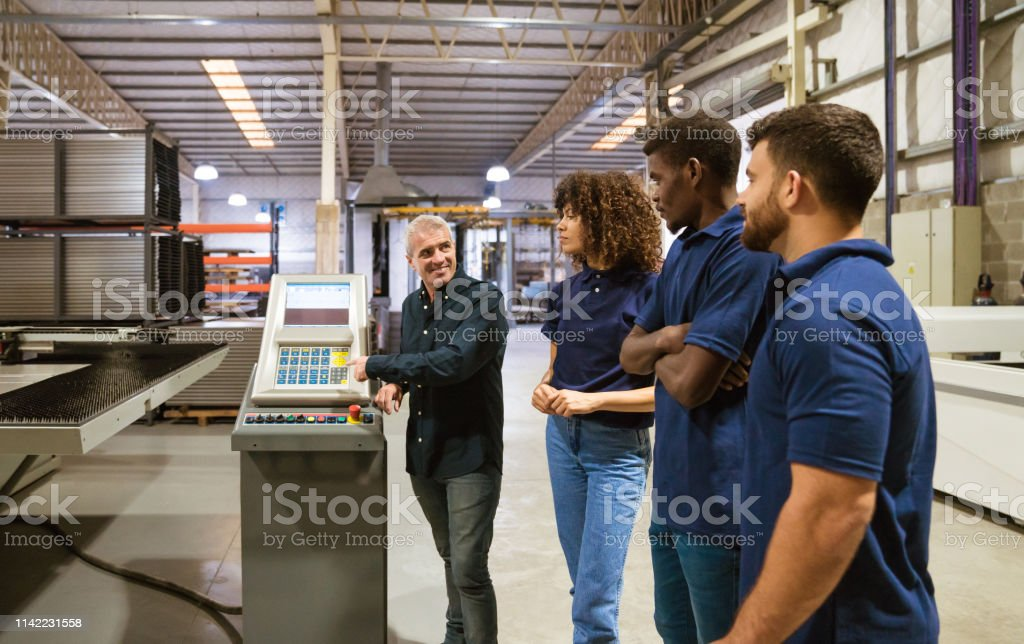 Instructor explaining trainees in industry Mature male instructor explaining trainees over puller machine. Confident engineer is with workers in industry. They are standing in factory. 20-24 Years Stock Photo
