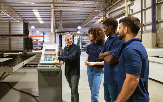 Instructor Explaining Trainees In Industry Stock Photo - Download Image Now