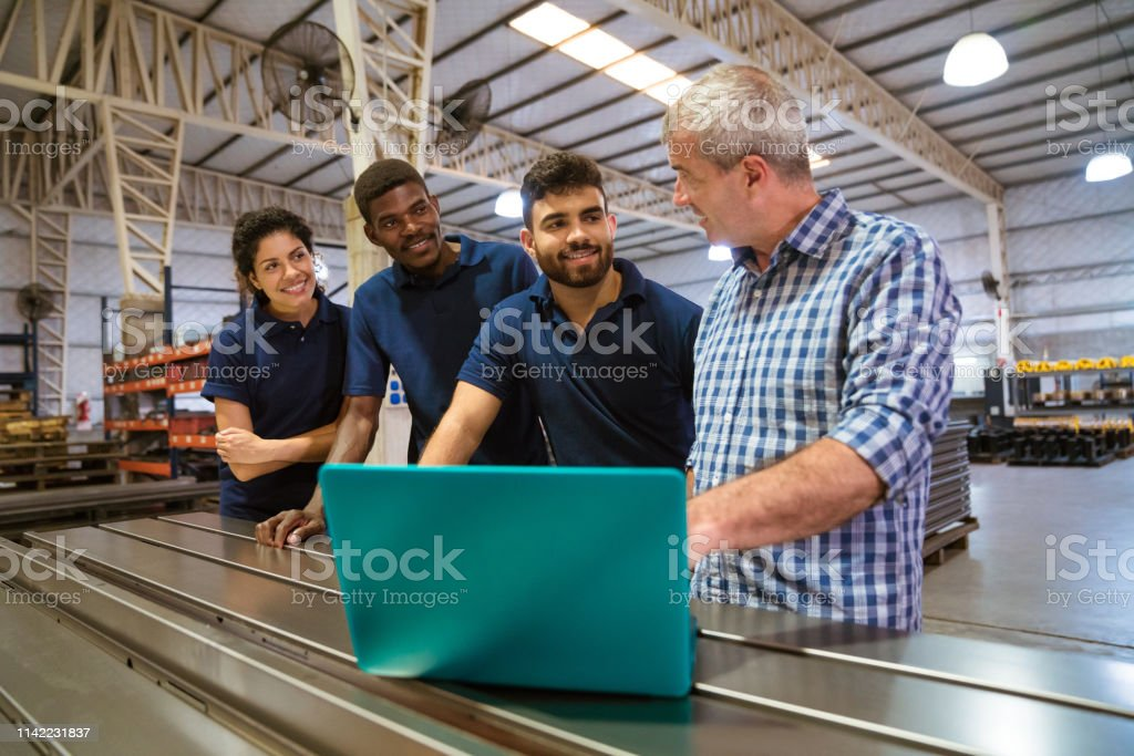 Instructor explaining trainees over laptop Male instructor explaining trainees over laptop. Confident apprentice are listening to engineer. They are standing in factory. 20-24 Years Stock Photo