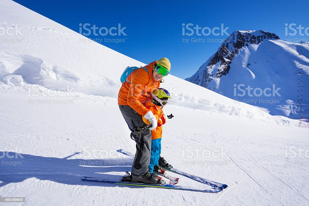 Instructor give ski lesson to little boy Instructor teaching little boy how to ski skiing with him on piste on mountain resort 2015 Stock Photo