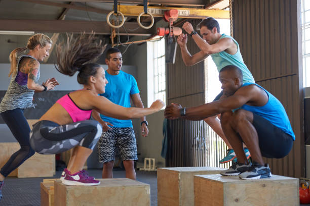 instructor giving encouragement while fit strong healthy people do box jumps - jumping zdjęcia i obrazy z banku zdjęć