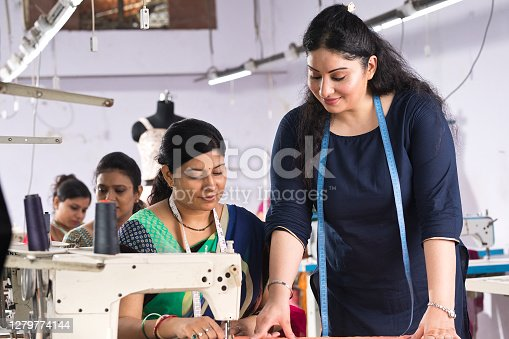 Two Indian women textile workers discussing and sewing garment on production line