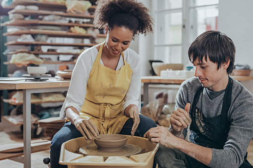 Instructor guiding pottery student  in art studio