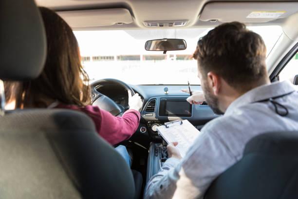 lehrer führen schüler um auto zu fahren - führerschein stock-fotos und bilder