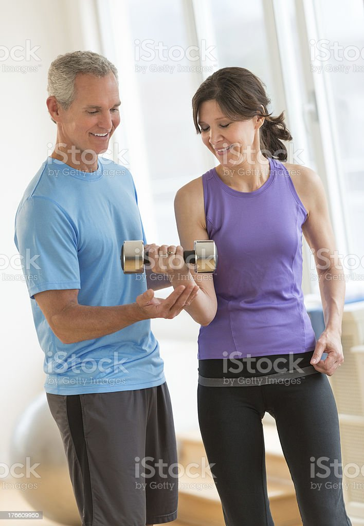 Instructor Guiding Woman In Weightlifting royalty-free stock photo