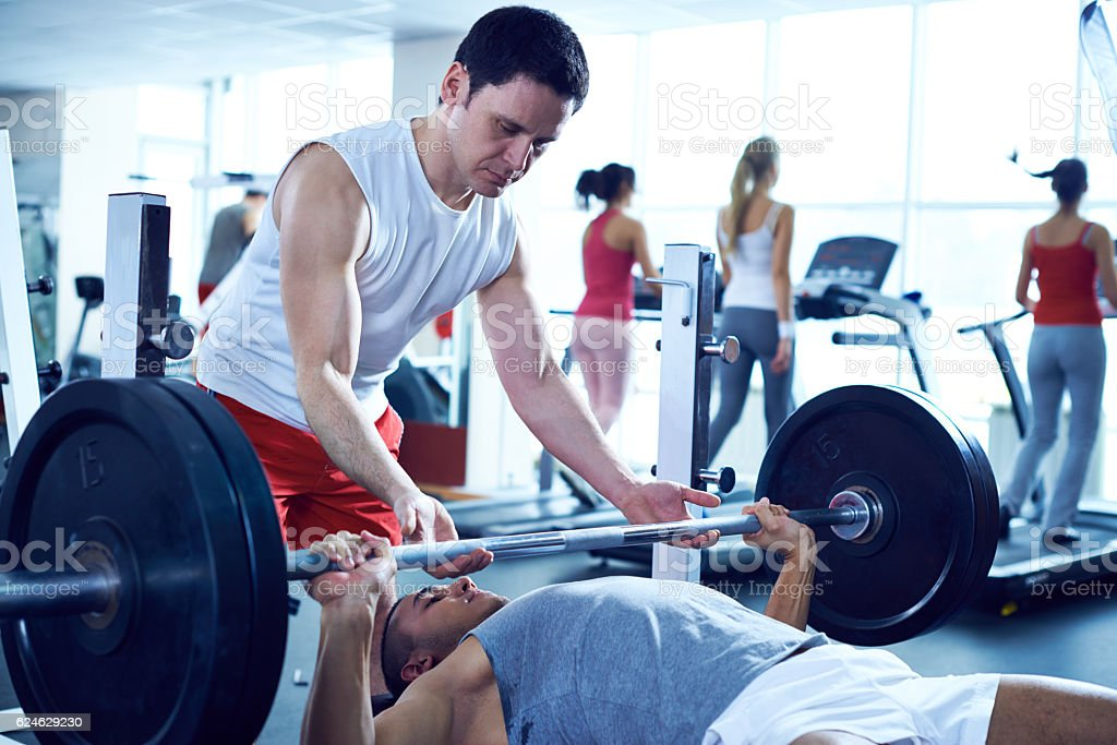 Instructor helping client to lift weights in gym stock photo