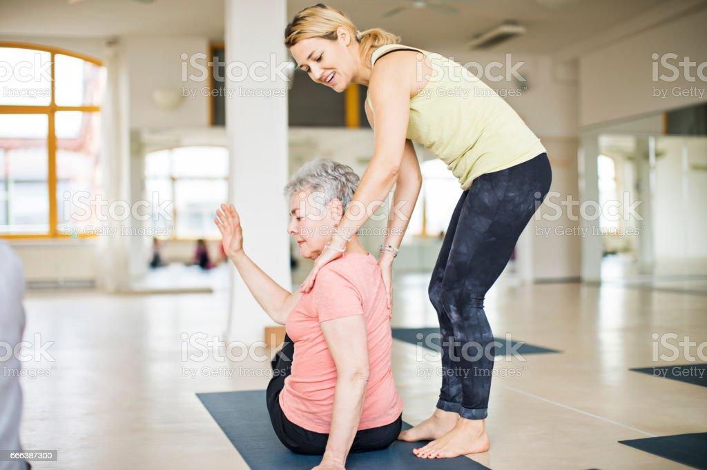 Lehrer helfen senior Frau dabei yoga – Foto