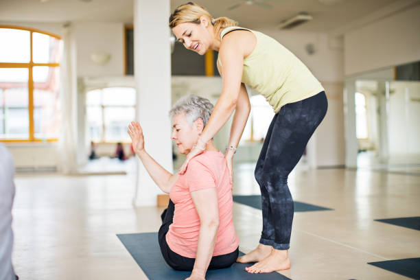 Instructor helping senior woman in doing yoga Full length of female instructor assisting senior woman in practicing yoga. Elderly lady is exercising in gym. They are in sportswear at health club. yoga instructor stock pictures, royalty-free photos & images