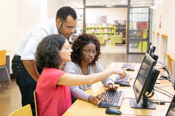 Kursleiter hilft Schülern im Computerunterricht – Foto