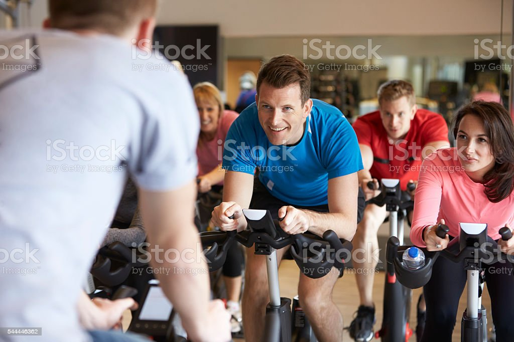Instructor in foreground with spinning class at a gym stock photo