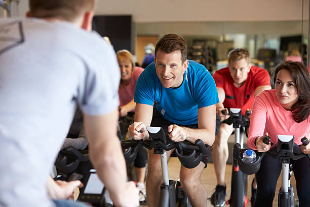 instructor in foreground with exercising class at a gym - ronddraaien stockfoto's en -beelden